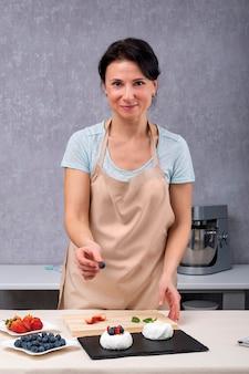 Porträt des konditoren während der zubereitung von kuchen. vertikaler rahmen.