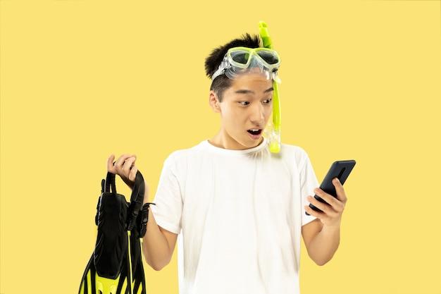 Porträt des koreanischen jungen mannes. männliches modell im weißen hemd und in der schutzbrille. flossen halten. konzept der menschlichen gefühle, ausdruck, sommerzeit, urlaub, wochenende.