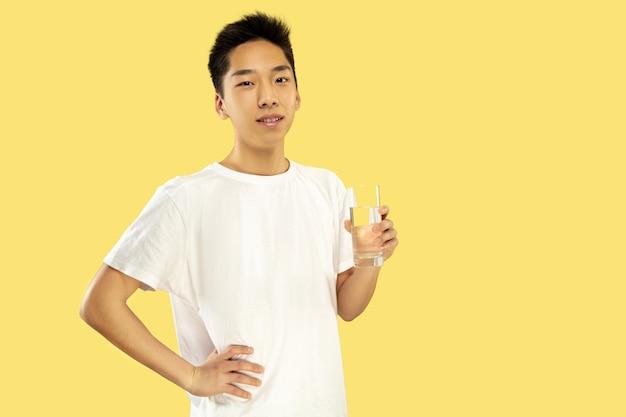 Porträt des koreanischen jungen mannes. männliches modell im weißen hemd. wasser trinken. konzept menschlicher emotionen, gesichtsausdruck. vorderansicht. trendige farben.