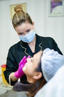 Porträt des kosmetikerarztes mit spritze in der hand