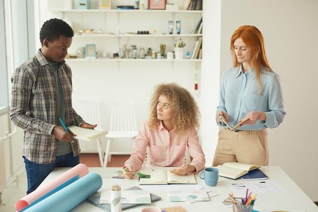 Porträt des kreativen geschäftsteams, das am entwurfsprojekt während des treffens im modernen weißen büro zusammenarbeitet