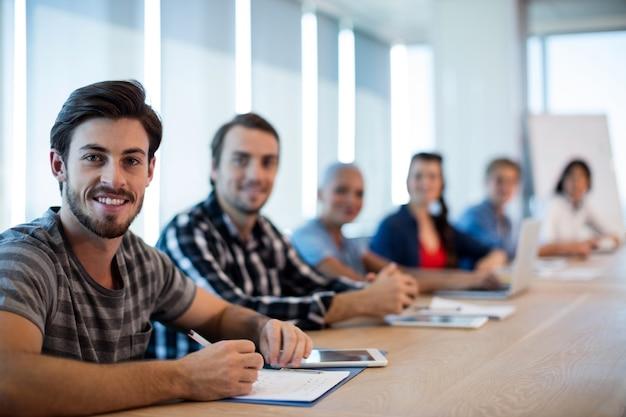 Porträt des kreativen geschäftsteams, das im konferenzraum im büro sitzt