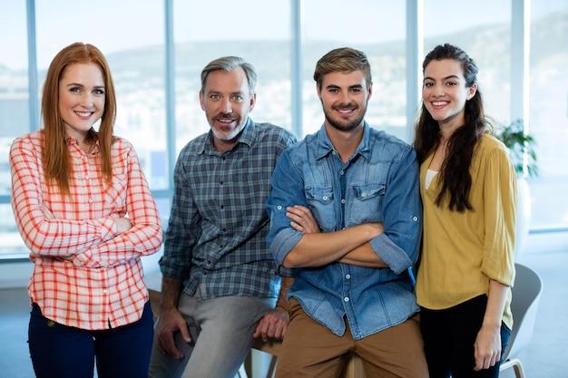 Porträt des kreativen geschäftsteams, das sich auf den tisch im büro stützt