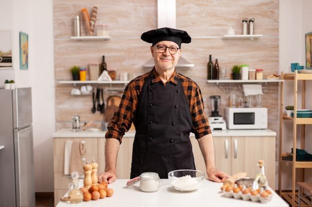 Porträt des küchenchefs mit knochen, der in die kamera schaut und lächelt. pensionierter älterer bäcker in küchenuniform, der gebäckzutaten auf holztisch zubereitet, bereit, hausgemachtes leckeres brot, kuchen und pasta zu kochen?