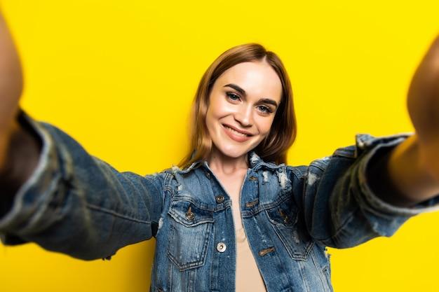 Porträt des kühlen fröhlichen mädchens, das selfie auf frontkamera lokalisiert auf gelber wand schießt