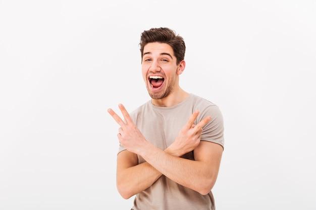 Porträt des kühlen kerls, der siegeszeichen mit zwei händen zeigt und glück ausdrückt, lokalisiert über weißer wand