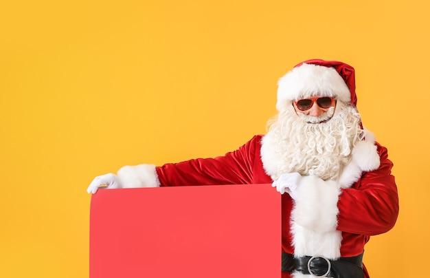 Porträt des kühlen weihnachtsmannes mit leerem plakat