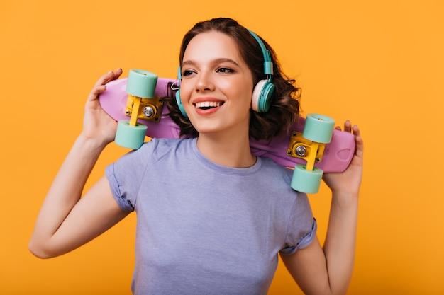 Porträt des lachenden fröhlichen mädchens, das musik genießt. romantische kaukasische dame mit buntem skateboard lächelnd.