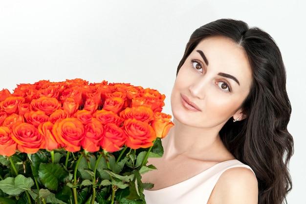 Porträt des lachenden rothaarigen mädchens mit orange rosen