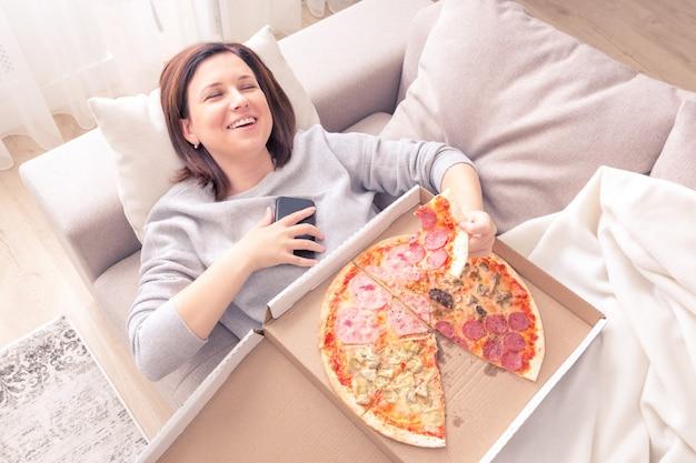 Porträt des lachens der jungen frau, die auf couch legt, pizza isst und telefonorangenton hält