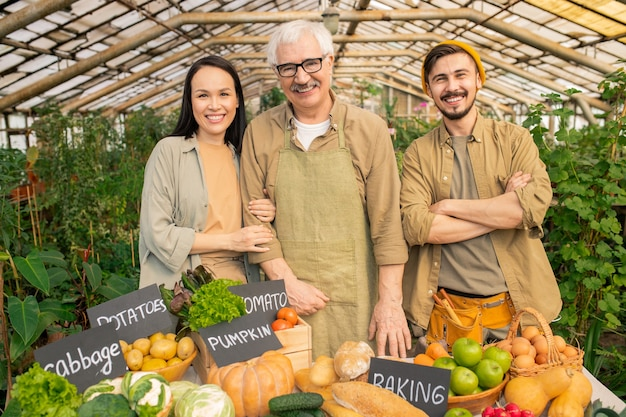 Porträt des lächelnden älteren gärtners und seiner jungen multiethnischen assistenten, die am tisch mit reifem gemüse am bauernmarkt stehen