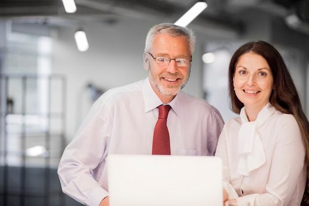 Porträt des lächelnden älteren geschäftsmannes und der geschäftsfrau mit laptop im büro