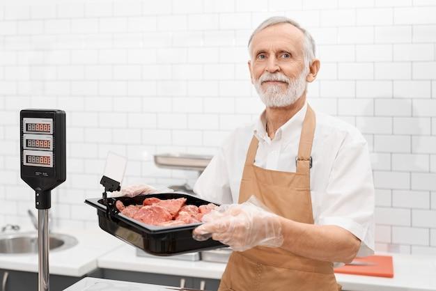 Porträt des lächelnden älteren männlichen metzgers, der ein stück frisches rotes rohes fleisch in den händen hält. fröhlicher mann hinter zähler des geschäfts, der fleisch zeigt und schüssel vom kühlschrank auf waage im supermarkt setzt.
