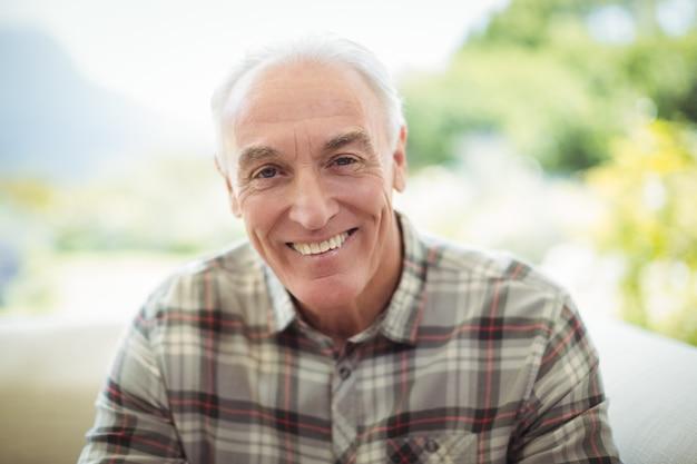 Porträt des lächelnden älteren mannes, der auf sofa im wohnzimmer sitzt