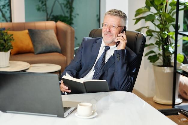 Porträt des lächelnden älteren unternehmers, der am schreibtisch sitzt und am telefon spricht und notizen im planer prüft