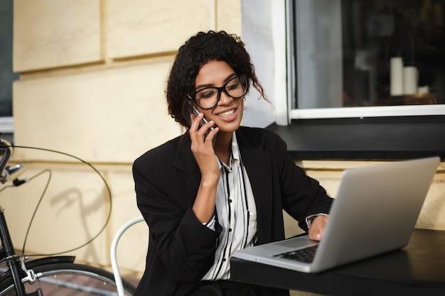 Porträt des lächelnden afroamerikanischen mädchens in den gläsern, die am tisch des cafés sitzen und am laptop arbeiten