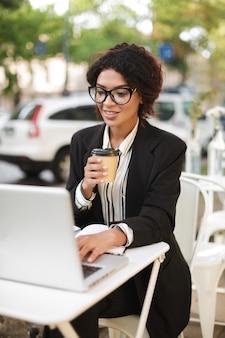 Porträt des lächelnden afroamerikanischen mädchens in den gläsern, die am tisch des cafés sitzen und an ihrem laptop arbeiten