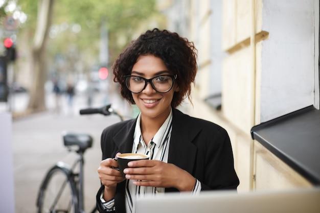 Porträt des lächelnden afroamerikanischen mädchens in den gläsern, die am tisch des cafés sitzen und tasse kaffee in den händen halten