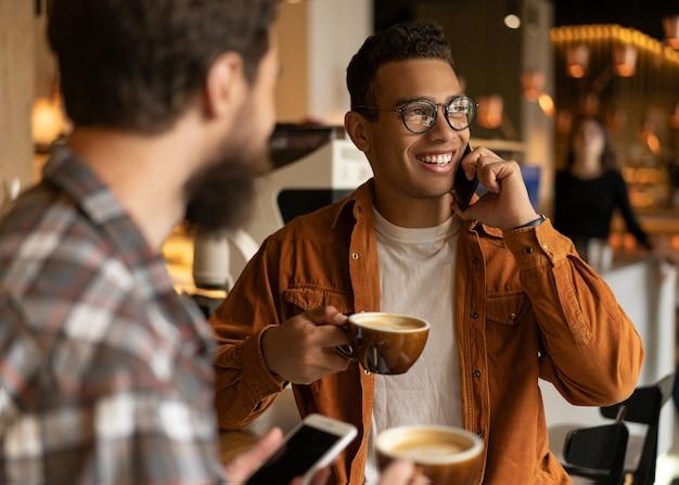 Porträt des lächelnden afroamerikanischen mannes, der auf handy spricht. hipster-freunde, die zusammen kaffee trinken, kommunizieren, lachen, smartphones benutzen, im café sitzen. kaffeepausen-konzept