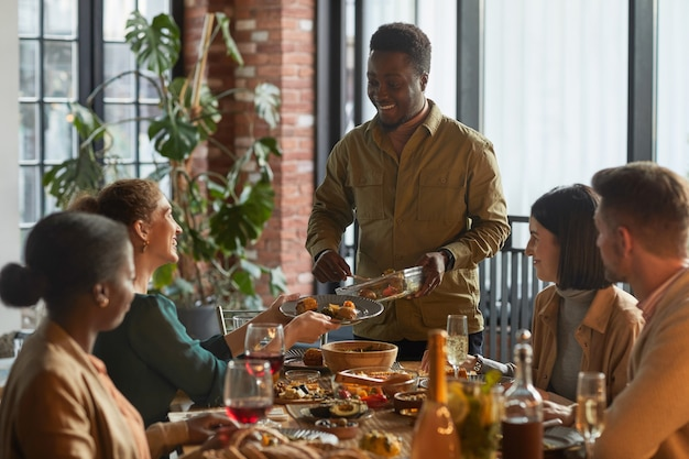 Porträt des lächelnden afroamerikanischen mannes, der essen serviert, während dinnerparty mit freunden und familie zu hause,