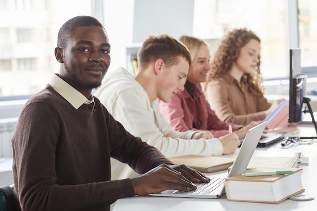 Porträt des lächelnden afroamerikanischen mannes unter verwendung des laptops und während des studiums mit einer gruppe von studenten im college