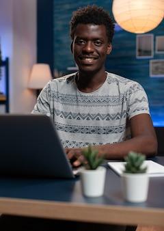 Porträt des lächelnden afroamerikanischen unternehmermanns, der managementinformationen durchsucht