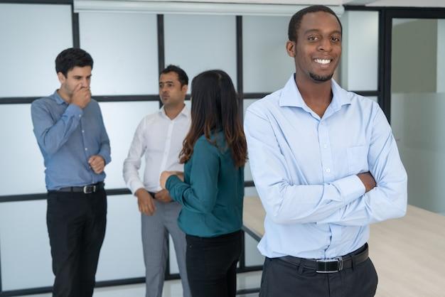 Porträt des lächelnden afroen-amerikanisch geschäftsmannes mit den armen faltete sich im konferenzsaal.