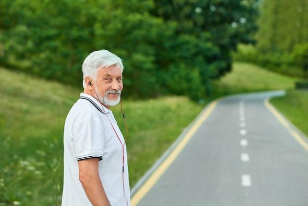Porträt des lächelnden alten mannes, der auf der rennbahn der stadt betrachtet kamera steht.