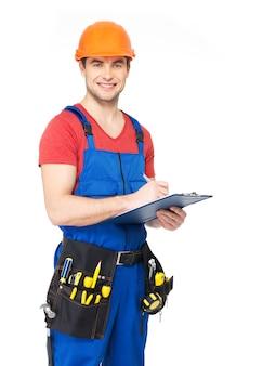 Porträt des lächelnden arbeiters mit werkzeugen, planen und schreiben der auf weiß isolierten notiz