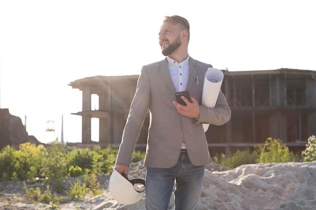 Porträt des lächelnden architektenmannes, der mobiltelefon und schutzhelm mit plan an der baustelle hält