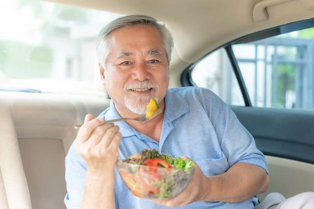 Porträt des lächelnden asiatischen älteren mannes, alter mann, älterer mann fühlen sich glücklich, essen frischen salat in seinem auto - lifestyle senior gesundes konzept