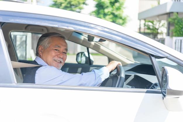 Porträt des lächelnden asiatischen älteren mannes, alter mann, älterer mann gute gesundheit beim autofahren