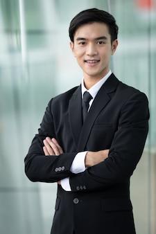 Porträt des lächelnden asiatischen geschäftsmannes im schwarzen anzug am büro im freien