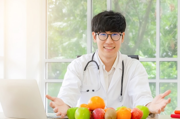 Porträt des lächelnden asiatischen männlichen ernährungswissenschaftlers mit gesunden frischen organischen früchten in seinem büro-, gesundheitswesen- und diätkonzept