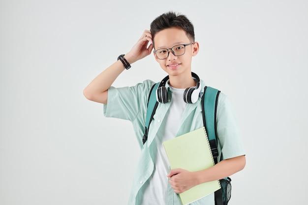 Porträt des lächelnden asiatischen schuljungen mit dem lehrbuch, das kopf kratzt und schaut