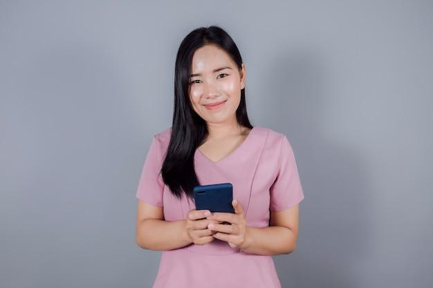 Porträt des lächelnden asiatischen teenagers benutzt handy oder smartphone auf grauem hintergrund