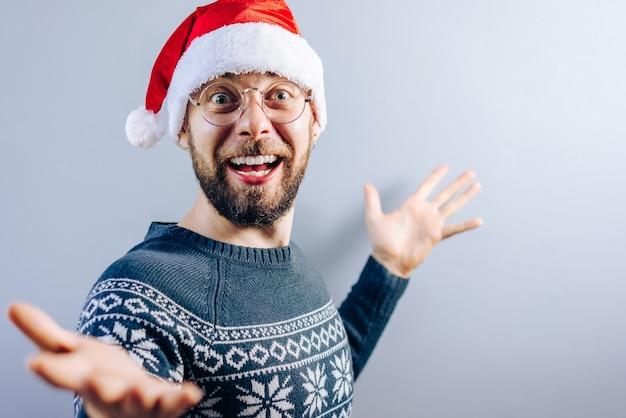 Porträt des lächelnden bärtigen kerls, der weihnachtsmütze, brille und blauen strickpullover mit leerer grauer wand auf dem hintergrund trägt