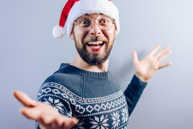 Porträt des lächelnden bärtigen kerls, der weihnachtsmütze trägt