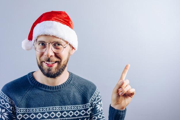 Porträt des lächelnden bärtigen kerls im weihnachtsmannhut und in den brillen, die zeigen
