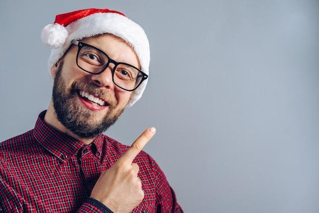 Porträt des lächelnden bärtigen kerls im weihnachtsmannhut