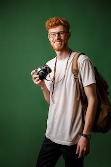 Porträt des lächelnden bärtigen lesekopf-hipsters mit retro-kamera und rucksack