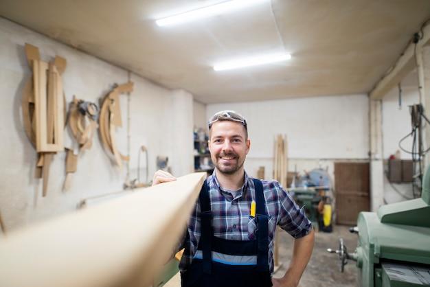 Porträt des lächelnden bärtigen tischlerholzarbeiters, der holzplanke auf schulter hält, bereit, sein nächstes projekt in der tischlerwerkstatt zu tun