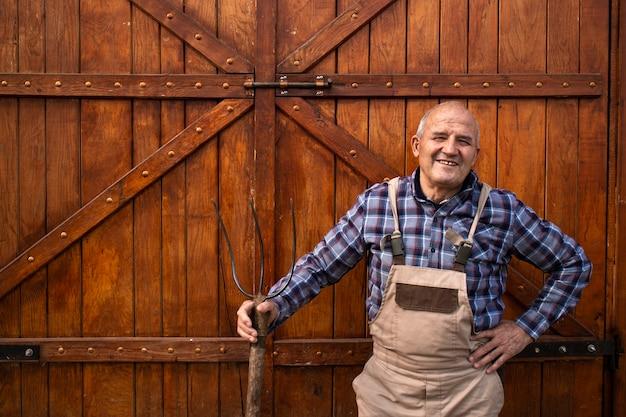 Porträt des lächelnden bauern, der heugabel hält und an hölzernen bauernhaus- oder nahrungsmittelkornspeichertüren an der haustierfarm steht.