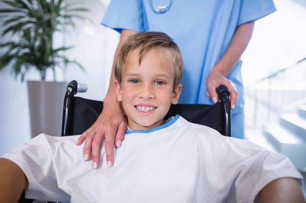 Porträt des lächelnden behinderten jungen im rollstuhl