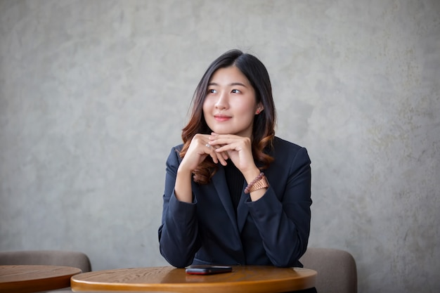 Porträt des lächelnden blickes der asiatischen jungen frau weg