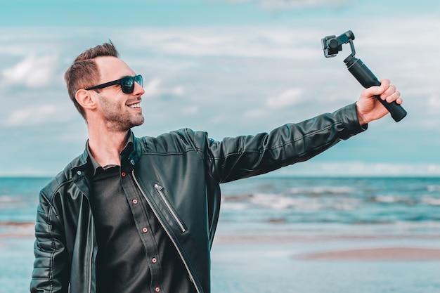Porträt des lächelnden bloggers in der sonnenbrille, die selfie macht oder video am strand streamen