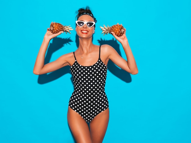 Porträt des lächelnden brunettemädchens im badeanzug und in der sonnenbrille der sommererbsenbadebekleidung.