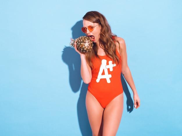 Porträt des lächelnden brunettemädchens in der roten badebekleidungskleidung des sommers und in der runden sonnenbrille. sexy frau, die frische ananas beißt. positive vorbildliche aufstellung
