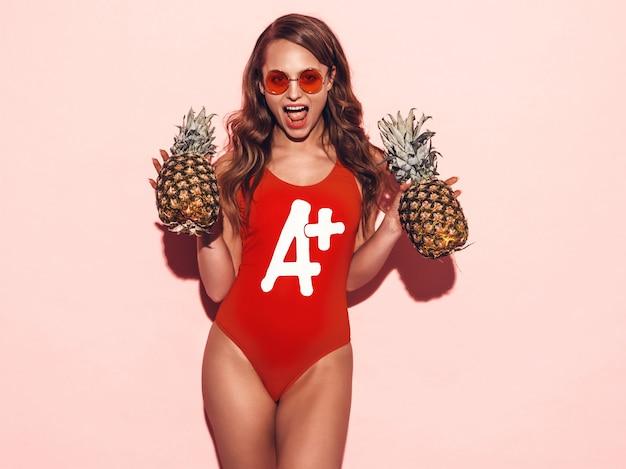 Porträt des lächelnden brunettemädchens in der roten badebekleidungskleidung des sommers und in der runden sonnenbrille. sexy frau mit frischen ananas. positive vorbildliche aufstellung