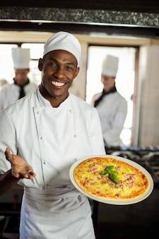 Porträt des lächelnden chefs pizza zeigend